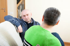 Men talking at home. Two adult friends talking at home royalty free stock image