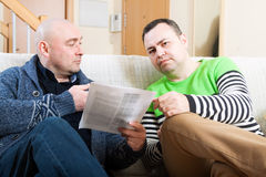 Men talking. Man sitting on sofa at home and talking with another man stock photography