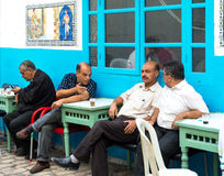 Men Talking Outside Cafe. Tunisian Men sitting at table outside Cafe having converstaion Royalty Free Stock Photo