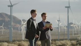 The men talking upon the project in the area of windmills stock footage