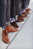 Men in tan and brown shoes with purple argyle socks stock photography