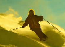 Men tear on ski. In yellow clouds of snow powder Royalty Free Stock Photography
