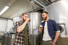 Men testing non-alcoholic craft beer at brewery. Production, manufacture, business and people concept - men testing and drinking non-alcoholic or craft beer at Stock Images