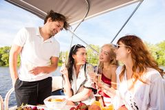 Men with three beautiful girls is drinking champagne on yacht royalty free stock image