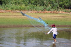 Men throw a net on the river. Stock Photography
