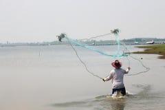 Men throw a net on the river. Stock Photos