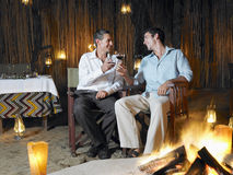 Men Toasting By Bonfire Royalty Free Stock Photography