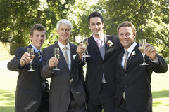 Men Toasting Champagne Flutes At Wedding. Portrait of happy four men toasting champagne flutes at wedding day Royalty Free Stock Photo