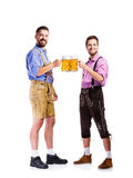 Men in traditional bavarian clothes holding mugs of beer Stock Photo