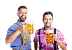 Men in traditional bavarian clothes holding mugs of beer Royalty Free Stock Photography