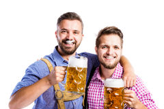 Men in traditional bavarian clothes holding mugs of beer Stock Photography