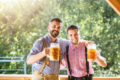Men in traditional bavarian clothes holding mugs of beer Royalty Free Stock Image