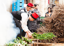 Men in traditional peasant dress cooking calsot Stock Images