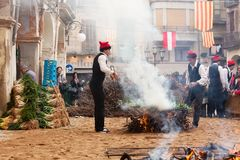 Men in traditional peasant dress cooking calsot on bonfire Royalty Free Stock Photo