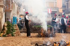 Men in traditional peasant dress cooking calsot on open fire Royalty Free Stock Images