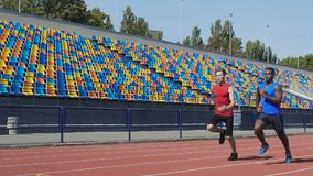 Men training strength and endurance at sport ground, preparing for competition stock video