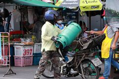 The men transport LPG gas by motorcycle to deliver to customers at the market