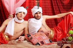 Men in turbans. Shot of two men in oriental costumes having a rest and smoking hookah Stock Photos
