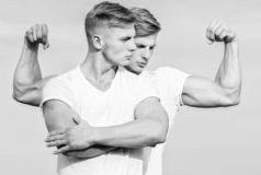 Men twins muscular brothers sky background. Men strong muscular athlete bodybuilder posing confidently in white shirts. Sport lifestyle and healthy body stock images