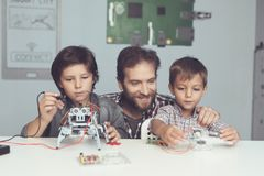 A man and two boys construct a robot. The man helps the boys with the assembly. A men and two boys construct a robot. The men helps the boys with the assembly Stock Photos