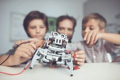 A man and two boys construct a robot. The man helps the boys with the assembly. A men and two boys construct a robot. The men helps the boys with the assembly Royalty Free Stock Photos