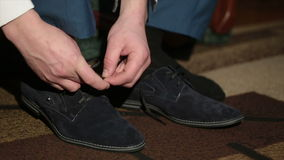 Men tying suede shoes laces stock video footage