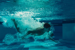 Men under water. Men are jumping into the swimming pool. Men are swimming under water in swimming pool Stock Photography