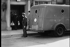 Men in uniform carrying money bags into Brinks truck stock video footage