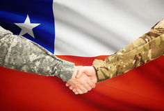 Men in uniform shaking hands with flag on background - Chile Stock Photos