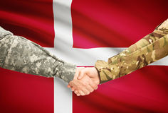 Men in uniform shaking hands with flag on background - Denmark Stock Photo