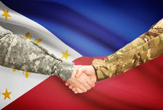 Men in uniform shaking hands with flag on background - Philippines Stock Photo