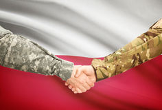 Men in uniform shaking hands with flag on background - Poland Royalty Free Stock Photography