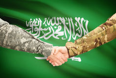 Men in uniform shaking hands with flag on background - Saudi Arabia Stock Images