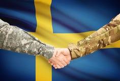 Men in uniform shaking hands with flag on background - Sweden Stock Images