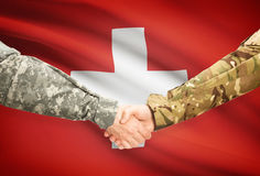 Men in uniform shaking hands with flag on background - Switzerland Royalty Free Stock Image