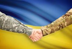 Men in uniform shaking hands with flag on background - Ukraine Stock Images