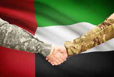 Men in uniform shaking hands with flag on background - United Arab Emirates Stock Photos