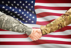 Men in uniform shaking hands with flag on background - United States. Soldiers shaking hands with flag on background - United States Stock Photography