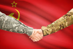 Men in uniform shaking hands with flag on background - USSR Royalty Free Stock Photos