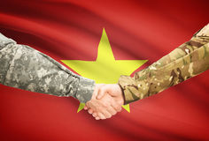 Men in uniform shaking hands with flag on background - Vietnam Royalty Free Stock Images