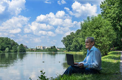 Men use the Internet in the summer on the nature Royalty Free Stock Image