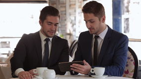Men use the tablet at lunchtime stock video footage