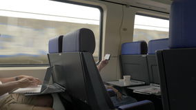 Men using cellphone and laptop in commuter train stock footage