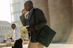 People busy using mobile phone while walking on street to office. Men using mobile phone while commuting to office. Businessmen leading a busy life using mobile Stock Photo