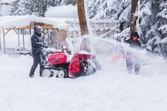 Men using snow removal machine. Hokkaido, Japan - 28 December 2017 - Unidentified man and his helper use their red snow removal machine to clear path way at a royalty free stock photos