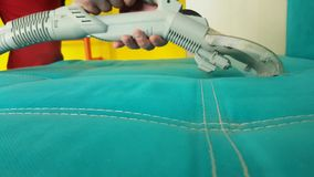Men vacuuming the couch with a steam cleaner uniform. Men vacuuming the couch with a steam cleaner worker uniform stock video