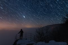 Men is on the viewpoint, under the startrail. Men is hiking on the mountain and standing on the viewopoint. He is watching the landscape under the startrail Royalty Free Stock Photography