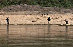 Men wait along the  Mekong River, Laos Royalty Free Stock Image