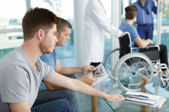Men waiting in lobby hospital. Men waiting in the lobby of a hospital royalty free stock image