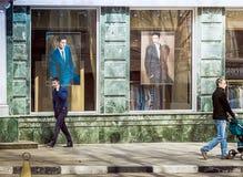 Men walk down the street near the men`s clothing store in Saratov royalty free stock photos